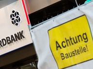 Blick auf einen Eingang zur HSH Nordbank, neben deren Eingang ein Schild Achtung Baustelle! häng. © dpa/picture alliance Foto: Daniel Bockwoldt