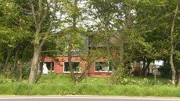 Wohnhaus der Einrichtung Friesenhof hinter Bäumen versteckt. © NDR