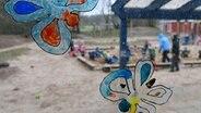 Auf einer Fensterscheibe sind bunte Schmetterlinge gemalt. Dahinter ist unscharf eine Spielfläche mit vielen kleinen Kindern zu erkennen. © dpa-Bildfunk Foto: Carsten Rehder