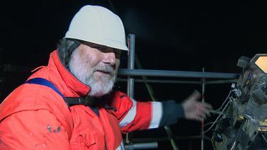 Ein Arbeiter seht bei Nacht auf einer Brücke neben einem koffergroßem zilindrischen Gerät. | NDR shmag