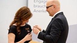 Die Sängerin Vicky Leandros erhält von Ministerpräsident Torsten Albig im Auftrag des Bundespräsidenten das Verdienstkreuz am Bande. © dpa - Bildfunk Foto: Carsten Rehder