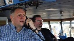 Lotse Martin Finnberg am Schiffstelefon auf der Brücke. © NDR Foto: Frank Hajasch