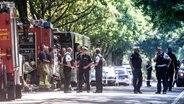 Einsatzkräfte stehen vor einem Bus im Lübecker Stadtteil Kücknitz, in dem am Nachmittag ein Fahrgast Mitreisende mit einem Messer attackiert hatte. © dpa-Bildfunk Fotograf: Markus Scholz