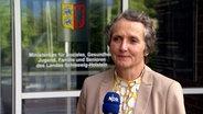Frau Dr. Anne Marcic steht vor dem Eingang des Ministerium für Soziales, Gesundheit, Jugend, Familie und Senioren des Landes Schleswig-Holstein © NDR