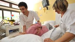 Pfleger bei der Arbeit mit einer Patientin. © Imago