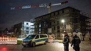 Polizisten während der Evakuierung in einer Neubausiedlung in Pinneberg. Im Hintergrund ein Kran, der umzukippen drohte. © dpa Foto: Daniel Bockwoldt