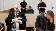 Ein Angeklagter sitzt im Gerichtssaal und verbirgt sein Gesicht hinter seiner Hand. © dpa-Bildfunk Foto: Markus Scholz