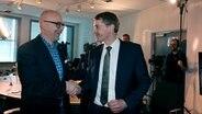 Torsten Albig und Daniel Günther begrüßen sich im Studio der NDR 1 Welle Nord zum Radio-Duell. © NDR Foto: Anna Baake