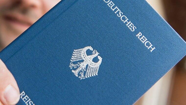 """Ein Mann hält ein Heft mit dem Aufdruck """"Deutsches Reich Reisepass"""" in der Hand. © dpa-Bildfunk Foto: Patrick Seeger"""
