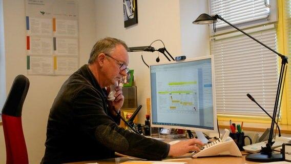 Un homme est assis à un bureau et est au téléphone.
