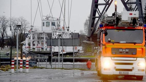 Die Rendsburger Schwebefähre hängt nach der Kollision mit einem Frachter beschädigt über dem Nord-Ostsee-Kanal. Die Feuerwehr ist vor Ort. © dpa-Bildfunk Foto: Carsten Rehder