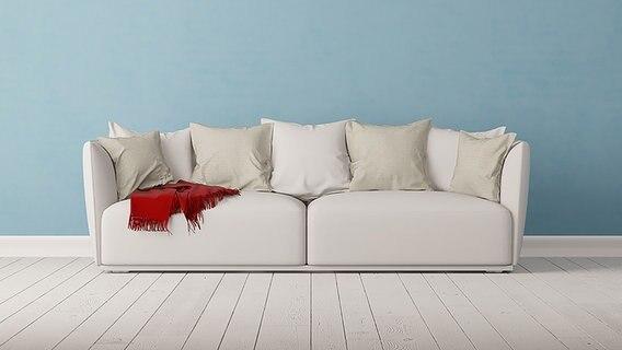 Auf einem weißen Sofa liegt eine rote Decke. © fotolia Fotograf: Robert Kneschke