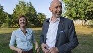 Simone Lange, die Oberbürgermeisterin von Flensburg und Alexander Ahrens, der Oberbürgermeister von Bautzen, stehen auf einer Wiese und lachen in die Kamera. © Simone Lange