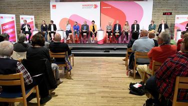 Die Kandidaten für den Vorsitz der SPD sitzen bei einer Regionalkonferenz auf dem Podium. | dpa-Bildfunk