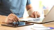 Ein Mann malt auf ein Tablet, während er parallel einen Laptop bedient. © imago images / Panthermedia Foto: Antonio Guillem