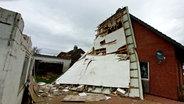 Ein Dach eines Einfamilienhauses in Eddelak ist abgerissen und hängt schräg an der Fassade. © WestküstenNews Foto: Karsten Schröder