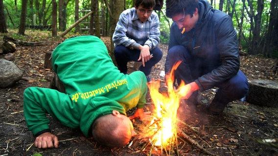Drei Männer entzünden ein Feuer. © NDR Fotograf: Hauke von Hallern