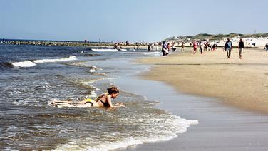 Blick auf den Strand von Westerland auf Sylt, wo viele Gäste am Wasser laufen © NDR Foto: Simone Dippel