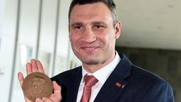Der ehemalige Profiboxer und heutige Bürgermeister der ukrainischen Hauptstadt Kiew, Vitali Klitschko, zeigt am 22.05.2015 in Kiel (Schleswig-Holstein) die Medaille zum Hermann-Ehlers-Preis. © dpa-Bildfunk Foto: Carsten Rehder