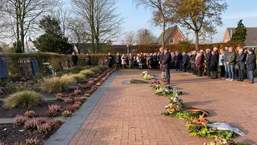 Zahlreiche Menschen stehen vor den Gräbernauf dem St. Petri Friedhof in Ladelund und gedenken den Opfern der Weltkriege. | NDR