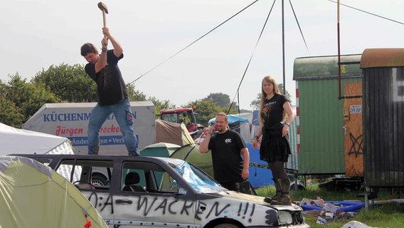Ein Mann zertrümmert mit einem Hammer ein Autowrack auf dem W:O:A 2012. © dpa-Bildfunk Foto: Wolfgang Runge