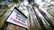 Auf einem Hinweisschild an einem Wald werden Kraftfahrer gebeten, Zigarettenkippen nicht aus dem Auto zu werfen. © NDR.de Fotograf: Patrick Pleul