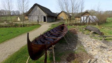 Ein Boot steht vor Häusern des Wikinger-Museums Haithabu. © dpa-Bildfunk Fotograf: Carsten Rehder