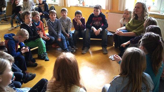 Kinder sitzen mit ihrer Lehrerin in einem Stuhlkreis. Mathe-Lehrerin Maike Hargasser unterrichtet 21 Grundschüler aller Klassenstufen in einer Lerngruppe. © NDR Foto: Astrid Wulf