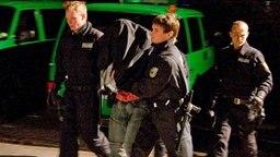 Polizisten führen einen mutmaßlichen Schleuser ab. © dpa Fotograf: Jens Holgerson