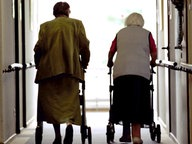 Zwei Senioren gehen mit Rollatoren durch einen Flur. © dpa Fotograf: Oliver Berg