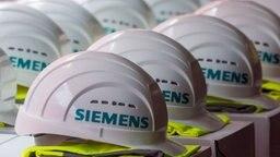 """aufgereihte weiße Schutzhelme mit der Aufschrift """"Siemens"""", darunter jeweils eine gefaltete gelbe Warnweste © dpa Bildfunk Fotograf: Jens Büttner"""