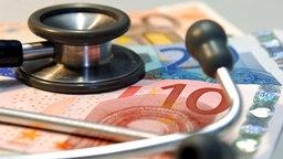 Ein Stethoskop liegt auf mehreren Geldscheinen. © dpa - Bildfunk Fotograf: Jan Woitas