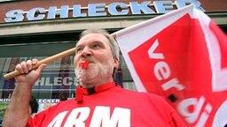 Streikender Einzelhandelsmitarbeiter mit einer Ver.di-Fahne © dpa Fotograf: Marco Führer