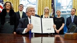"""Präsident Donald Trump hält ein unterzeichnetes """"National Security Presidential Memorandum"""" gegen die Terrororganisation Islamischer Staat im Oval Office in Washington in den Händen. © dpa Bildfunk Fotograf: Alex Brandon"""