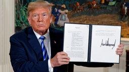 Donald Trump, Präsident der USA, zeigt ein unterzeichnetes Präsidentschaftsmemorandum in die Kamera. © dpa bildfunk Foto: Evan Vucci