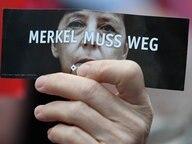 """Demonstranten protestieren am 06.09.2017 in Finsterwalde (Brandenburg) während einer Wahlkampfveranstaltung der CDU auf dem Marktplatz gegen Bundeskanzlerin Angela Merkel (CDU). Ein Demonstrant hält eine Karte mit der Aufschrift """"Merkel muss weg"""". © dpa bildfunk Foto: Ralf Hirschberger"""