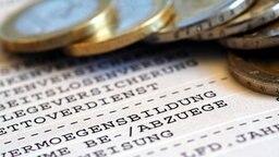 Euromünzen auf einer Gehaltsabrechung © picture-alliance/dpa Themendienst Foto: Jens Schierenbeck