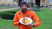 Schüssel-Schorse steht vor Schloss Bückeburg und hält einen Teller mit Currywurst und Pommes. © NDR Foto: NDR