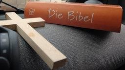 Symbol Kreuz und Bibel © dpa
