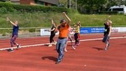 Schüssel-Schorse macht mit einer Gruppe Frauen Sport auf dem Sportplatz. © NDR