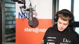 Ben Dolic sitzt vor dem Mikrofon bei stars@ndr2 und schaut nach unten © NDR 2 Foto: Gilbert Lake
