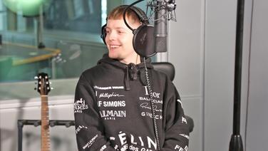 Ben Dolic hinter dem Mikrofon. Er schaut lächelnd zur Seite. © NDR 2 Foto: Gilbert Lake