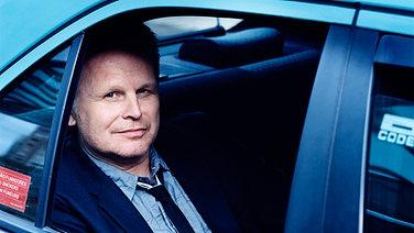 Herbert Grönemeyer sitzt auf der Rückbank eines Autos und guckt durch das geöffnete Fenster nach draußen (Promofoto).  Foto: AntonCorbijn
