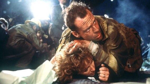 """Der amerikanische Schauspieler Bruce Willis als New Yorker Cop John McClane und Bonnie Bedelia als seine Ehefrau Holly in einer Szene des Action-Thrillers """"Stirb Langsam"""" (""""Die Hard"""") von 1988. © picture-alliance / dpa"""