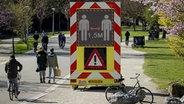 Ein Schild im Vondelpark warnt vor einem Abstand von 1,5 Metern wegen des Koronavirus.  Foto: ROBIN VAN LONKHUIJSEN-dpa