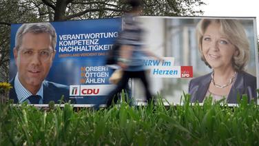 Wahlplakate der CDU mit ihrem Spitzenkandidaten Norbert Röttgen und der SPD mit Ministerpräsidentin Hannelore Kraft. © dpa-Bildfunk Foto: Martin Gerten dpa/lnw