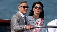 George Clooney und seine Frau Amal Alamuddin stehen auf einem Boot. ©  picture alliance / dpa Foto:  Alessandro Di Meo