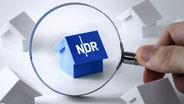 Eine Lupe deutet auf ein blaues Papierhäuschen mit dem Logo des NDR auf dem Dach, das zwischen anderen weißen Papierhäuschen steht. © fotolia.com Foto: Kenishirotie
