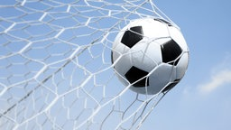 Ein Fußball fliegt in das Netz eines Tores. © fotolia.com Foto: joesive47
