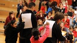 Zwei Mädchen malen zwei spielenden Kontrabassisten etwas auf den Rücken. © NDR Fotograf: Marcus Krueger